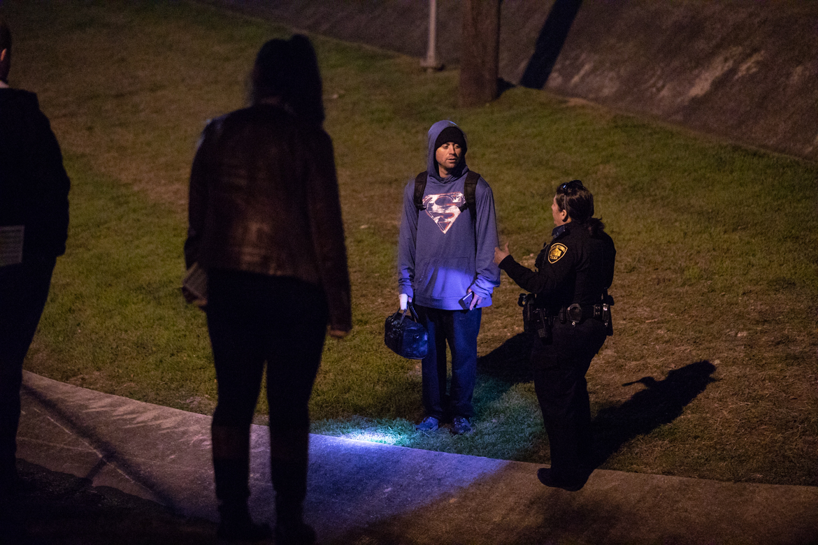 Participants and a police officer in the Point in Time Count approach a homeless man, asking if he needs help.