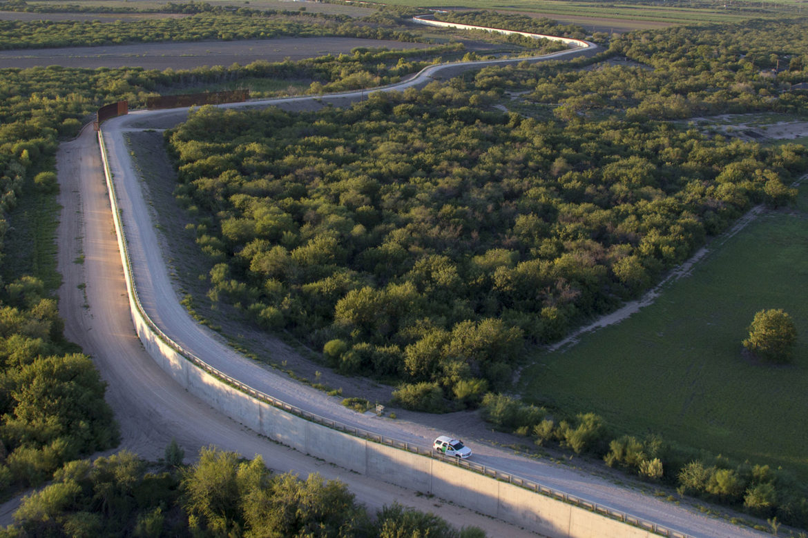 A United States Border Patrol vehicle patrols on watch at a border fence along the a South Texas border in the Rio Grande Valley.