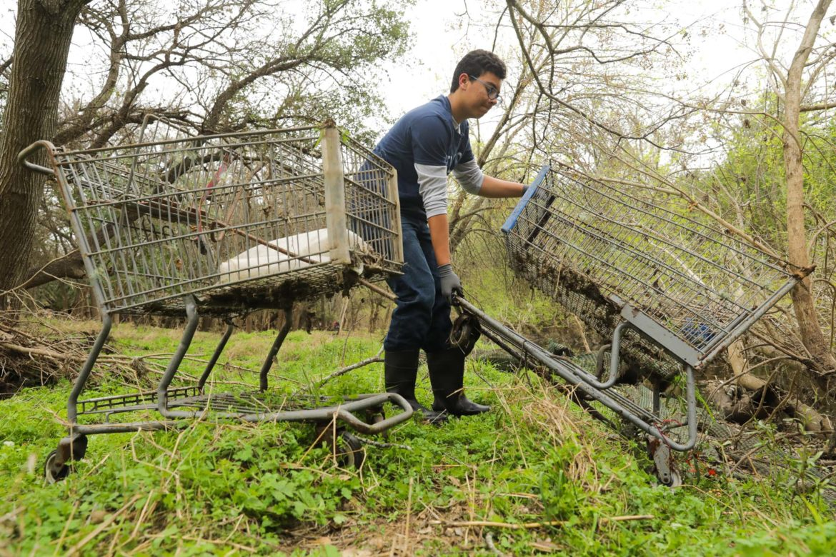 Joshua Caudill extracts two shopping carts from Salado Creek during the annual Basura Bash in efforts to clean up waterways throughout San Antonio.