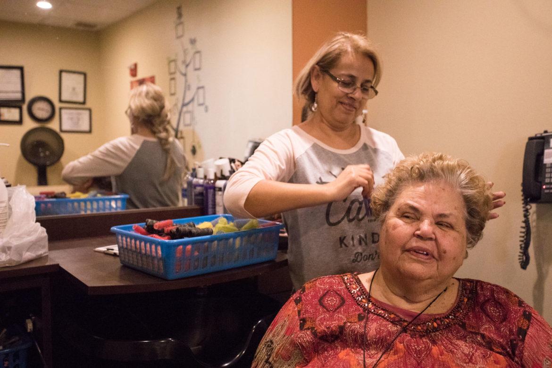 Hairdresser Guillermina Irene Davila Rivera combs out Marilyn Fassett's hair.