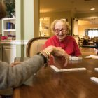 Christine Wicker (right) plays dominoes in the lobby of building 1.