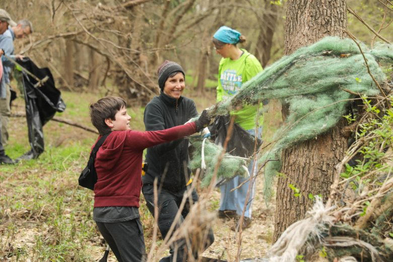 Volunteers Paula Pebsworth and eight year old David Barsalou pulls tangled fabric from trees along the creek.