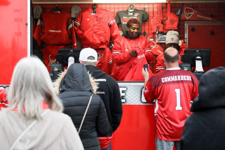 Desiree Mejia sells Commanders merchandise to newly established fans of the team.
