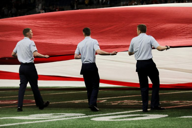 Members of the United States Airforce stretch out a football field sized American flag before the game.