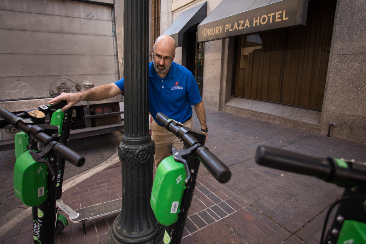 John Jacks, Director of the Center City Development and Operations Department, places a scooter upright.
