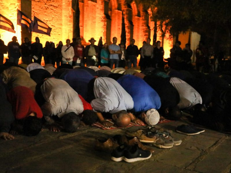 Dozens of Muslims kneel in front of San Fernando Cathedral in Main Plaza for their post-sunset prayer as equality flags are flown a gathered crowd forms a circle behind them for protection.