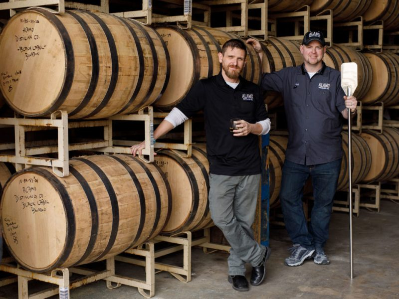 Alamo Distilling Co. Co-Founders Daniel Taylor and Noel Burns (right) stand for a photo outside barrels of their signature black label bourbon.