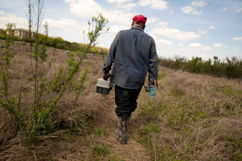 """Fisherman David Garza treks through matted grass to thick brush on his way to his fishing hole at Panther Springs Creek Dam. His biggest fish caught was a 16"""" 13 pound bass."""