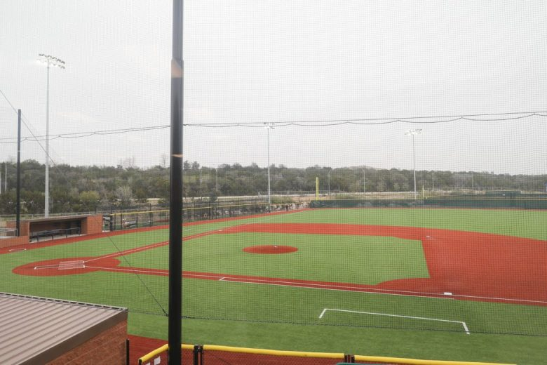 A large baseball field with overheating lighting allows for evening games.