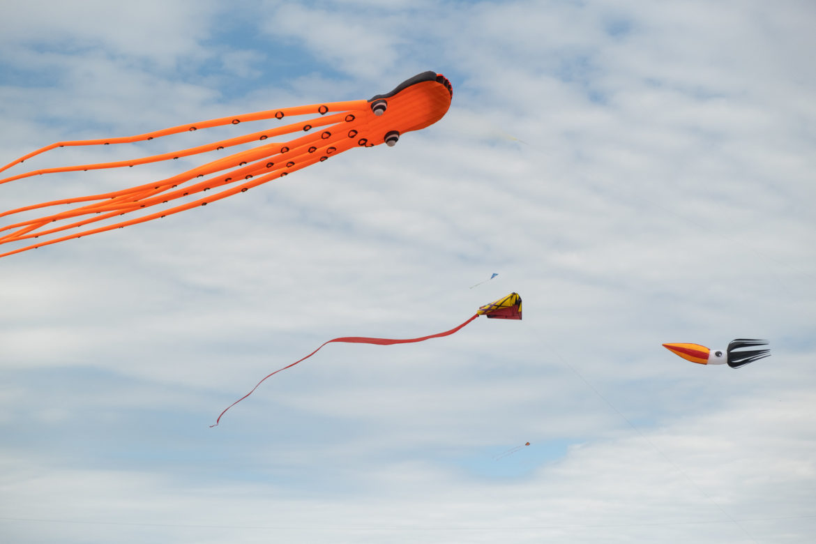 """Giant kites guided by professional team """"Go Big or Go Home"""" fly through the air during the festival."""