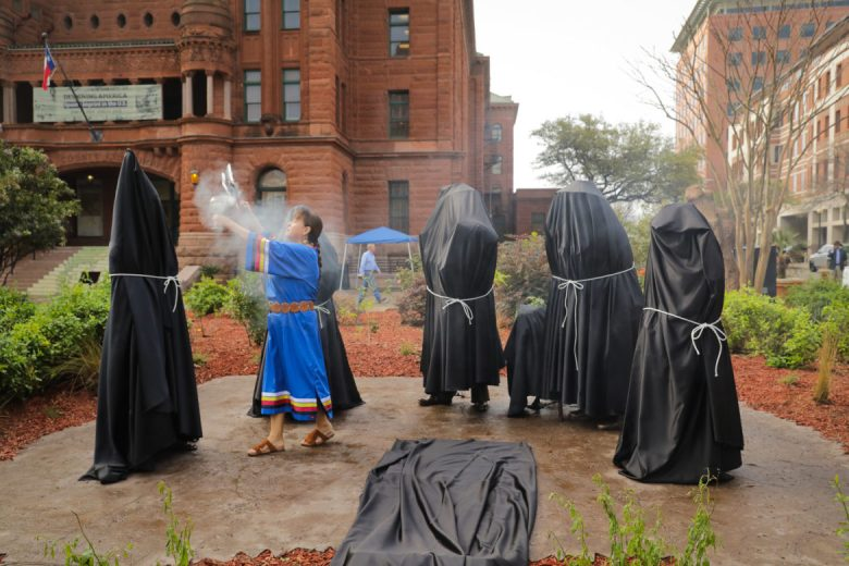 Victoria Salas cleanses the monuments before they are unveiled in front of the Bexar County Courthouse.