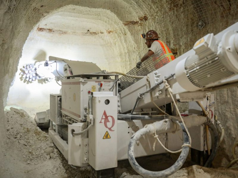 A roadheader machine is used to excavate small pieces of the tunnel walls before tunnel boring machine is dropped in.