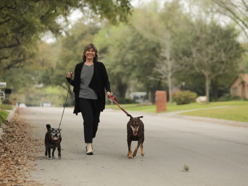 Susan Korbel walks her dogs through a residential Castle Hills street.