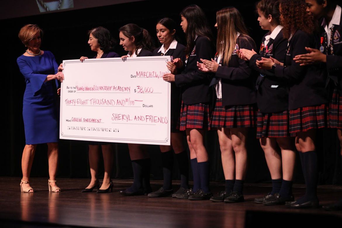 Former City Manager Sheryl Sculley (right) presents a check for $38,000 to the Young Women's Leadership Academy.