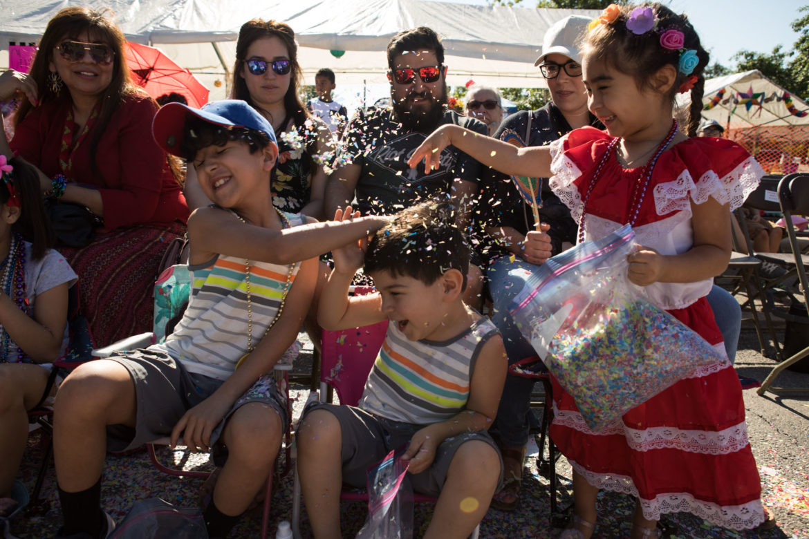 (From left) Noah, 9, Jameson, 5, and Madison, 4, throw confetti on one another during the Battle of Flowers parade.