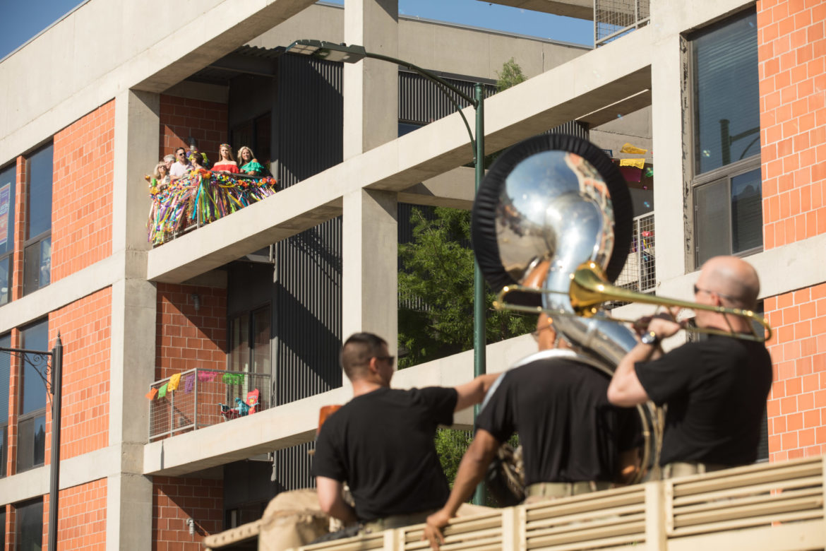 Residents of 1221 Broadway Lofts watch the parade pass by.