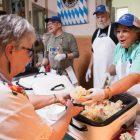 Beth Hannemann serves German sausage and sauerkraut to guests at Gartenfest.