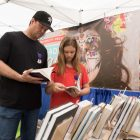 (From left) Lane Hudson and Audrey, 11, browse books inside the Trinity University Press tent.