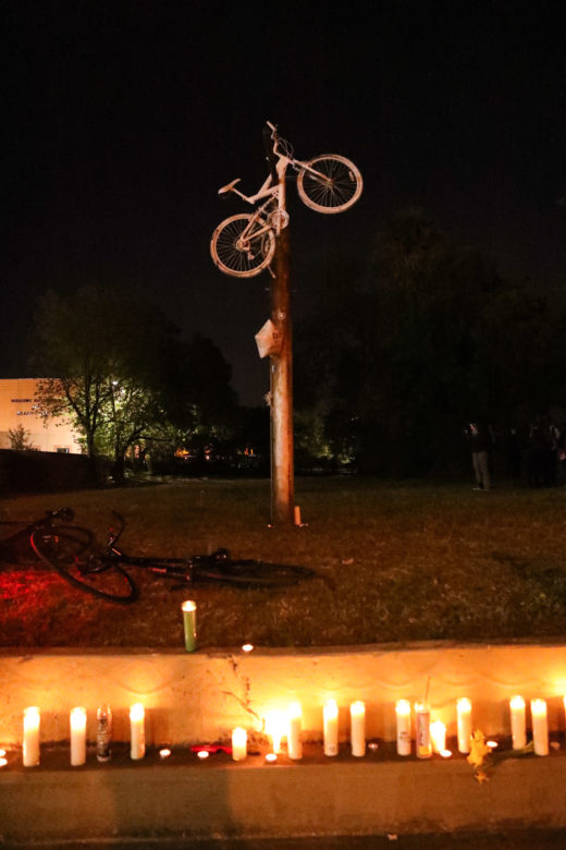 A white bike and candles are placed at the site of where Tito Bradshaw was hit on his bike.