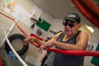 Charlie Mata coaches from the ropes alongside the ring at Advocates Youth Gym.