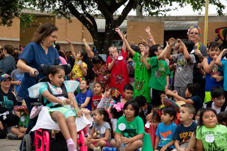 Children raise their hands as confetti falls from above following the run.