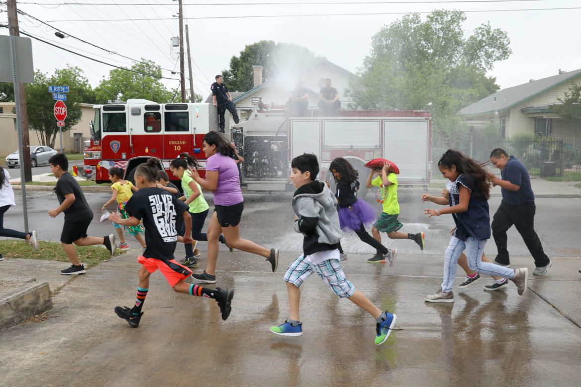 Beacon Hill Academy students, parents, and teachers run around the school during the Fiesta Run which includes being sprayed with water by local firefighters.
