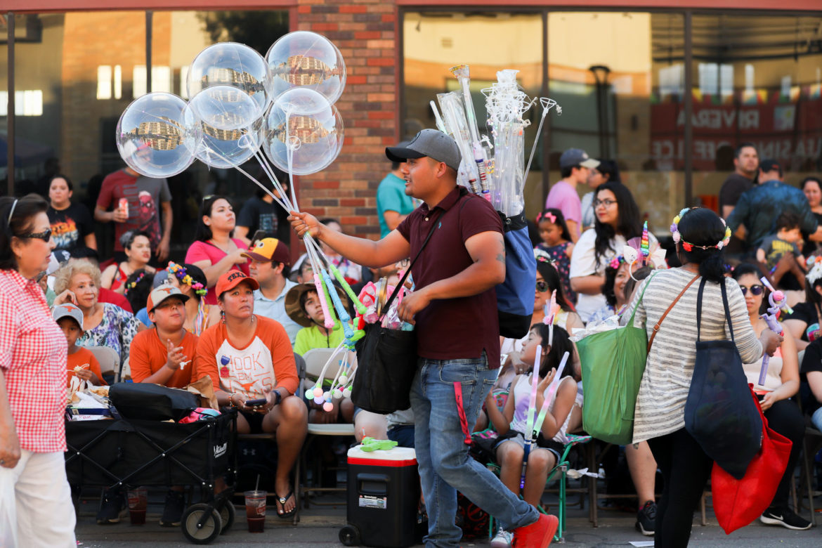 A vendor sells balloons and light sticks during the Fiesta Flambeau Parade in 2019. Fiesta is responsible for an annual economic impact of more than $300 million.