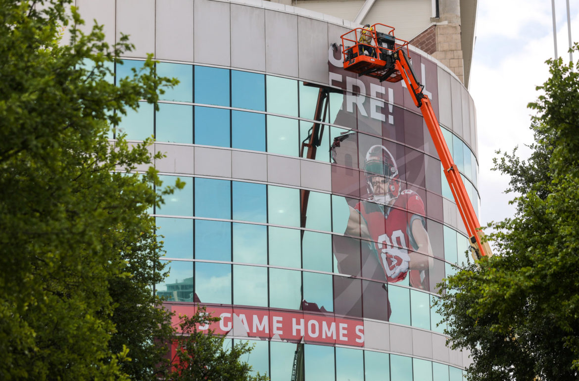 A sign advertising the San Antonio Commanders home games is removed from the Northwest corner of the Alamodome following the league folding midseason.