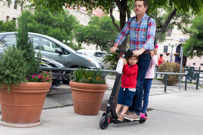 A family rides three on a Bird scooter on a downtown San Antonio sidewalk.