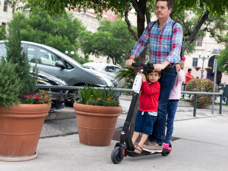 A family rides three on a Bird scooter on a downtown San Antonio sidewalk.