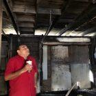 Jason Mata, who runs the Advocates Boxing Youth Program, examines the fire damage.