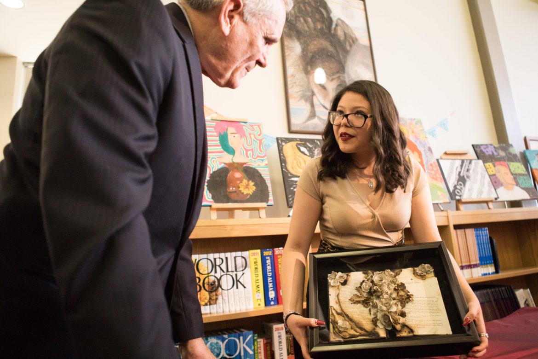 "Highlands High School junior Yiovanna Plascencia explains her art piece ""A New Beginning"" to U.S. Representative Lloyd Doggett (D-San Antonio)."