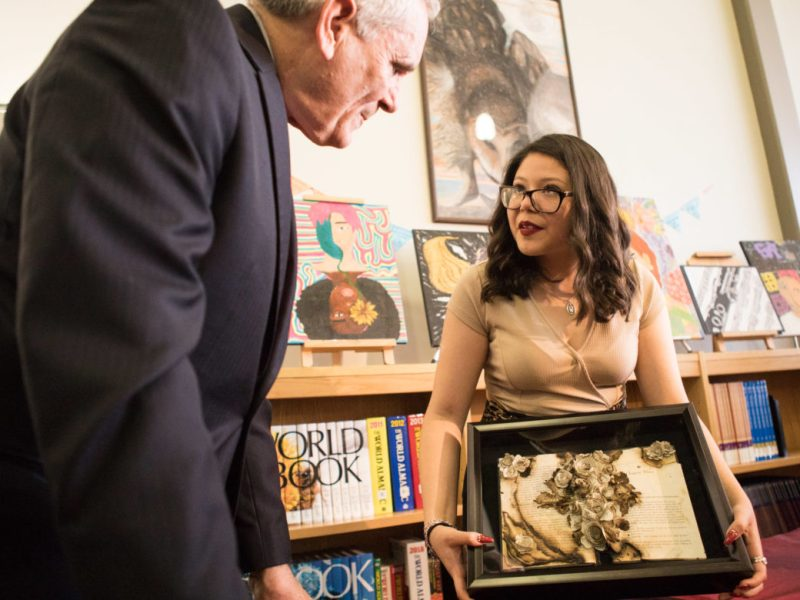 "Highlands High School junior Yiovanna Plascencia explains her art piece ""A New Beginning"" to U.S. Representative Lloyd Doggett (D-San Antonio)."