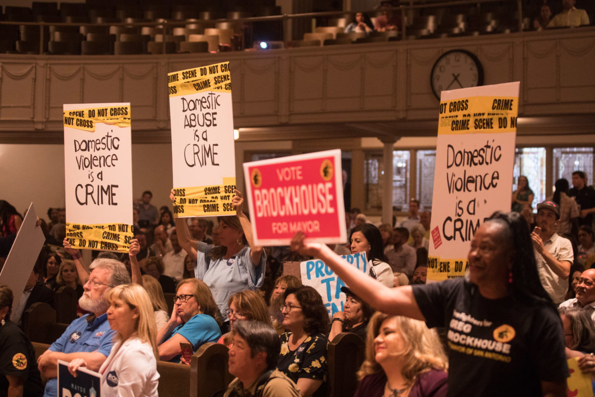 Audience members hold signs in support of their favorite candidate.