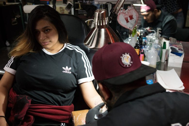 Diamond Huerta (left) receives her first tattoo by Raul Ortiz.