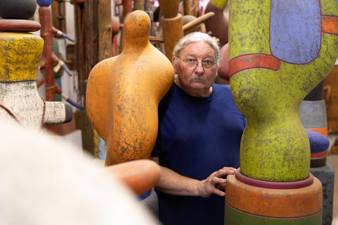 Danville Chadbourne stands with a room full of finished pieces in his home studio.