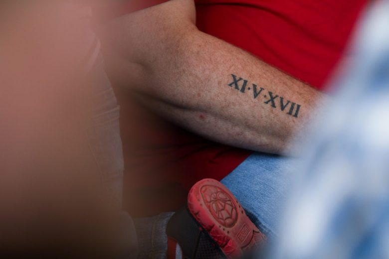A man in the congregation's tattoo marks the date in which the massacre took place.