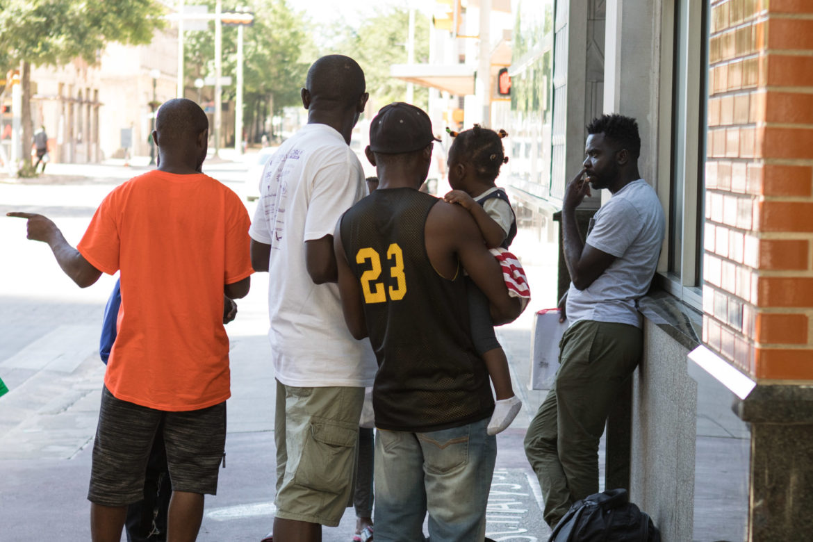African migrants stand outside of the resource center.