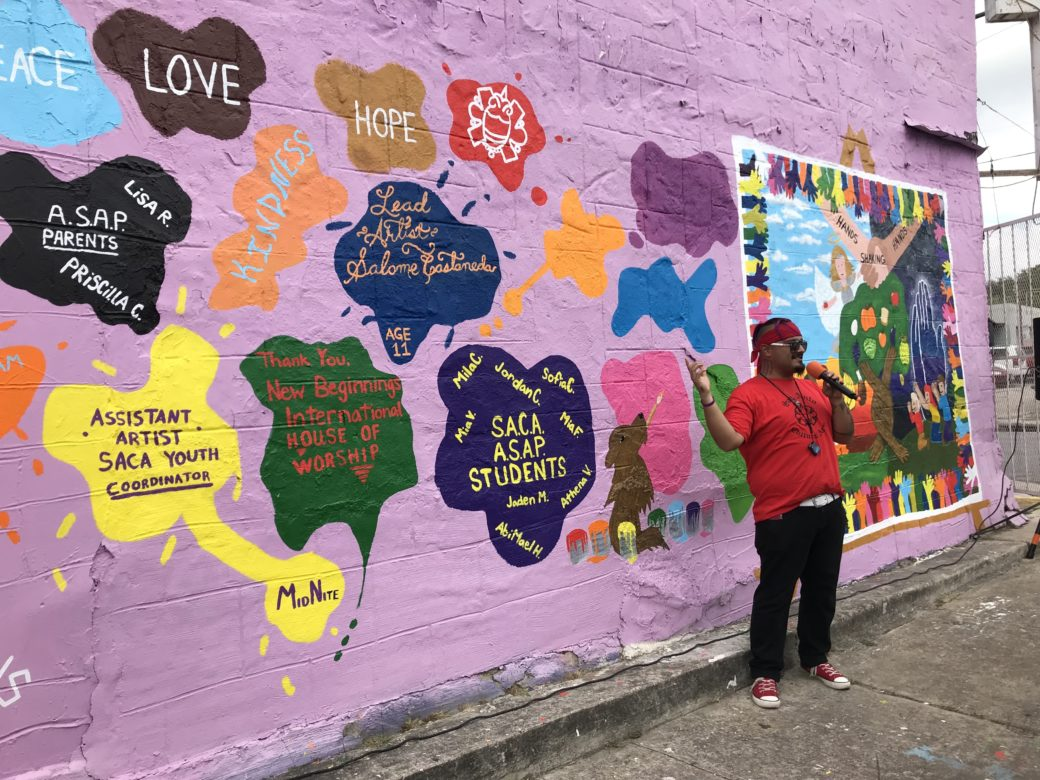 MidNite Flores, youth coordinator at San Anto Cultural Arts, speaks in front of a youth mural unveiled at the International House of Worship on the West Side.