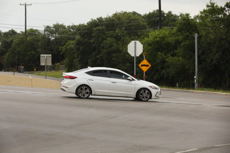 A vehicle drives at the intersection of Farm Road 1560 and Riggs Road.