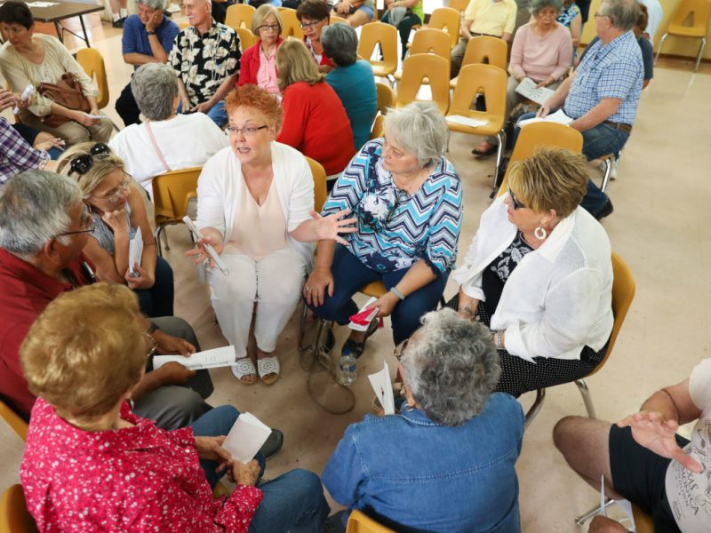 Residents and commuters of Helotes gather in small groups to discuss ways TXDOT can repair a curve at Farm Road 1560 and Riggs Road.