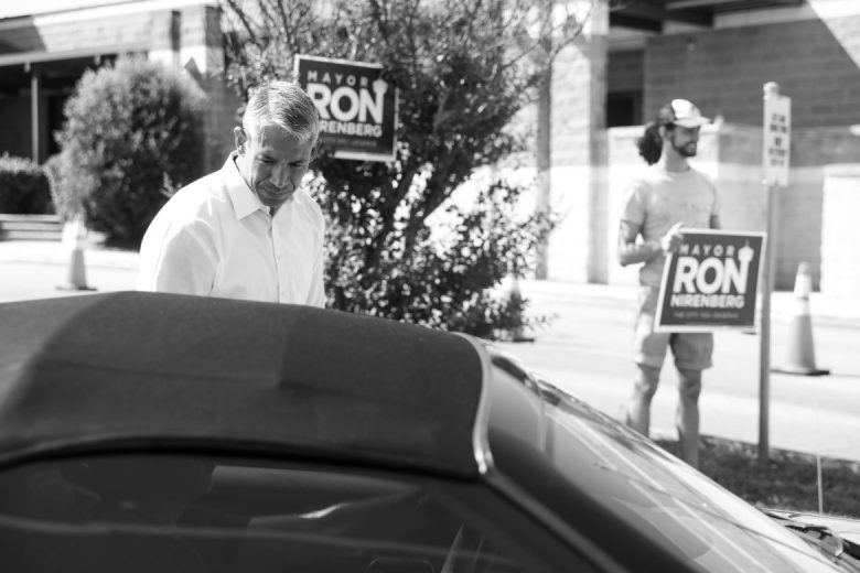 Mayor Nirenberg speaks with voters outside of Huebner Road Elementary school as volunteer James Dykeman holds a sign in support.