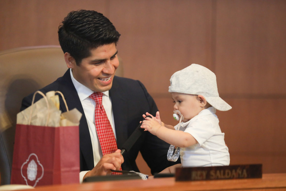 Outgoing councilman Rey Saldaña spends time with his son Eli behind the dais on his last day of Council.