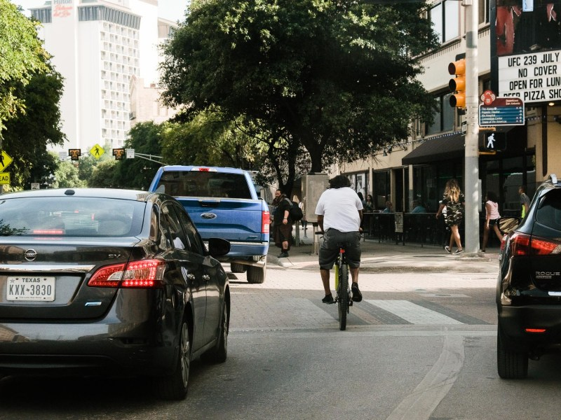 A downtown cyclist navigates Broadway Street, a major North - South artery connecting neighborhoods to the center city.