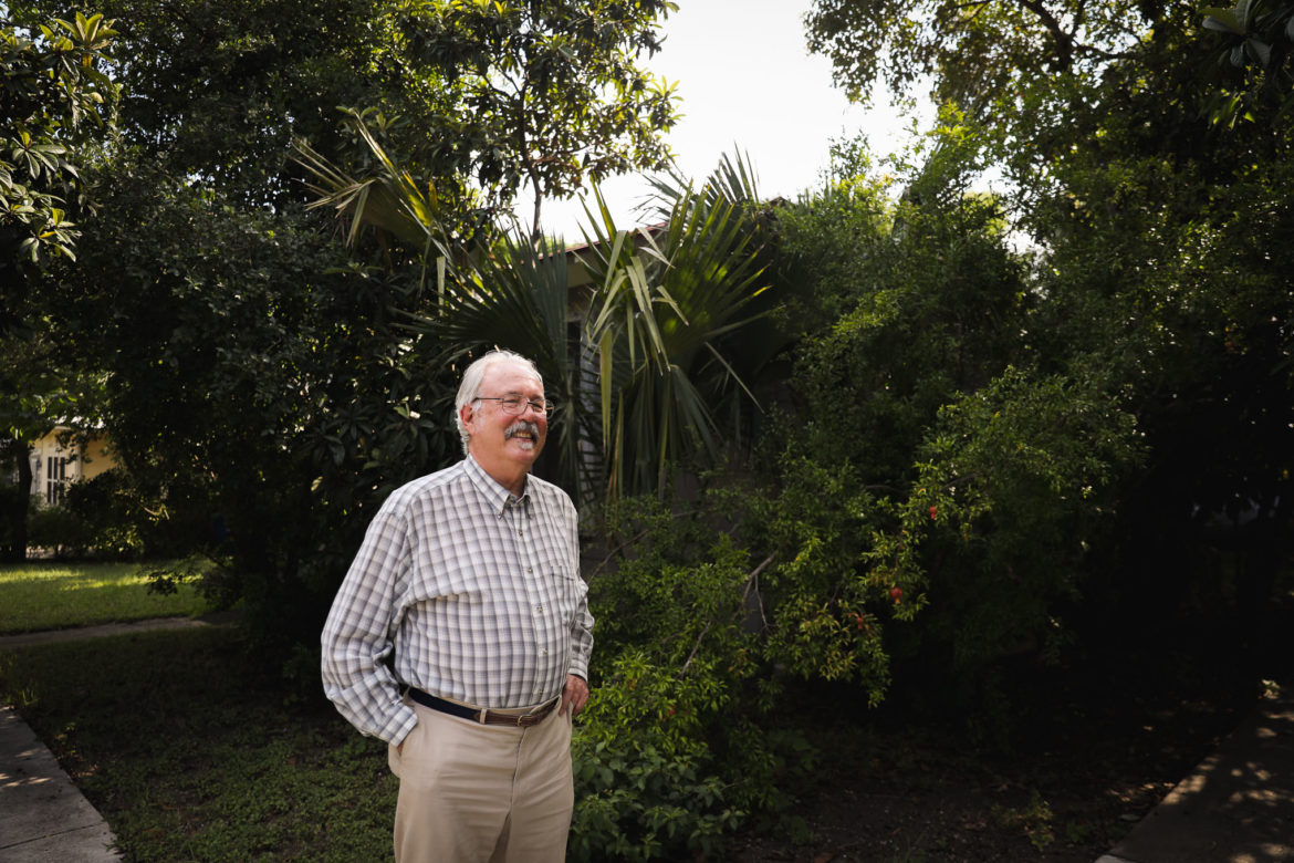 Don Mathis stands outside his Laurel Heights home and the pomegranate and loquat trees that produce on his property.