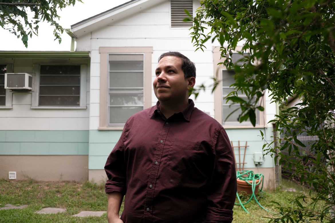 Dominic Gonzalez stands under his ornamental pomegranate tree in the backyard of his Los Angeles Heights home.