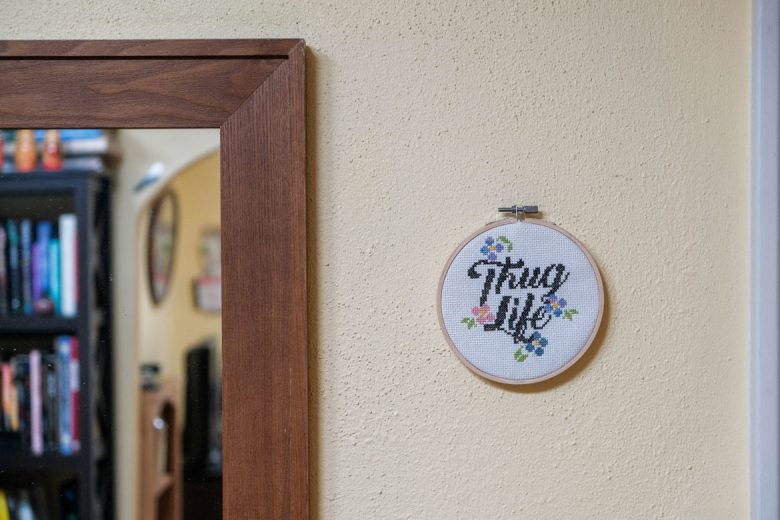 A 'Thug Life' needle point is hung inside Dominic's home.