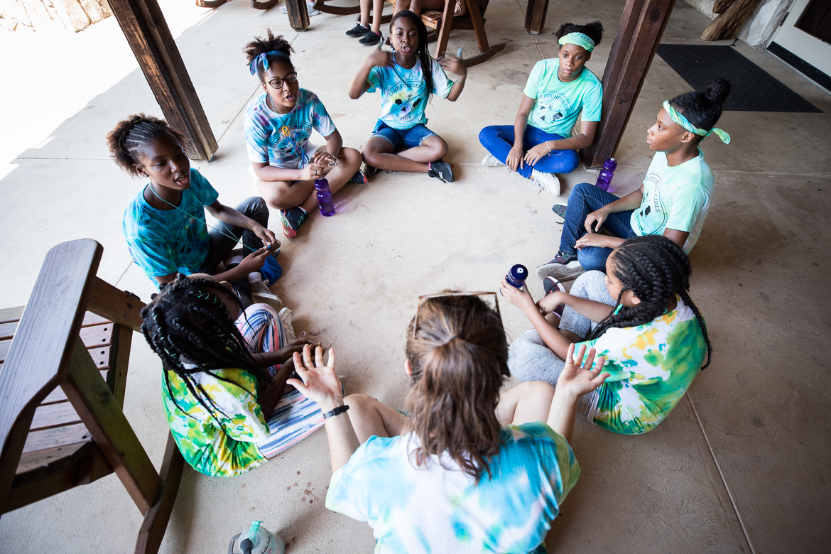 Camp Founder Girls sit together while playing a game before lunch.