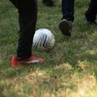 The soccer ball is kicked through the park.