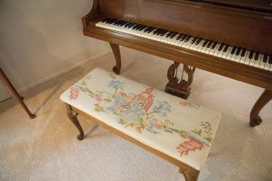 The needlepoint piece attached to the piano seat in Janet Alyn's home was created by her mother.
